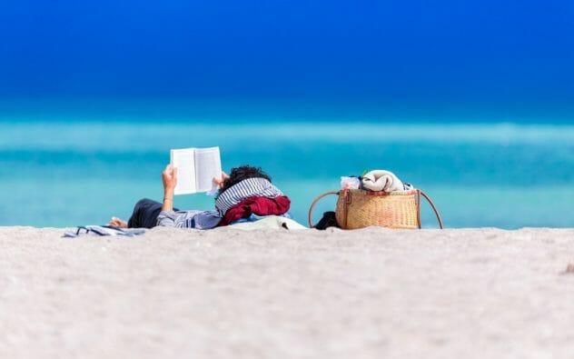 Hombre leyendo en la playa